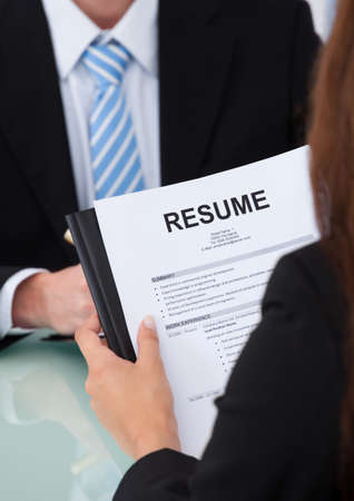 job vacancies: Cropped image of female candidate holding resume at desk during interview Stock Photo