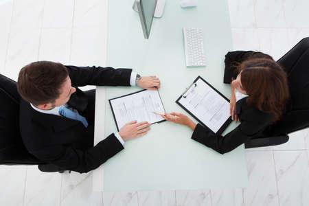 puesto de trabajo: Justo encima de tiro de joven empresaria entrevistar candidato var�n en oficina Foto de archivo