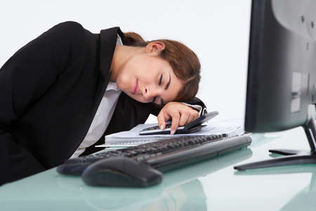 Stressed young businesswoman leaning at computer desk in office photo