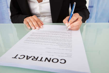 Midsection of young businesswoman signing contract paper at office desk photo