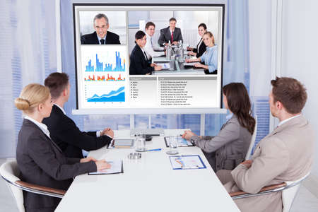 video conference: Group of business people attending video conference at table in office