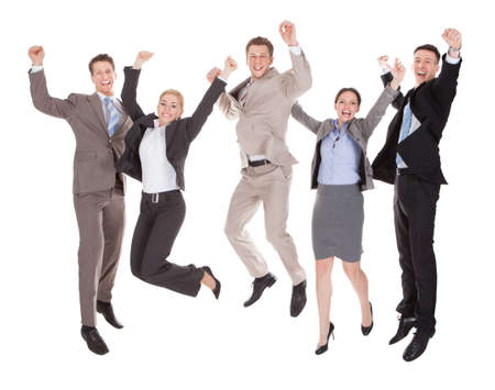 Full längd av glada unga företagare hoppar över vita