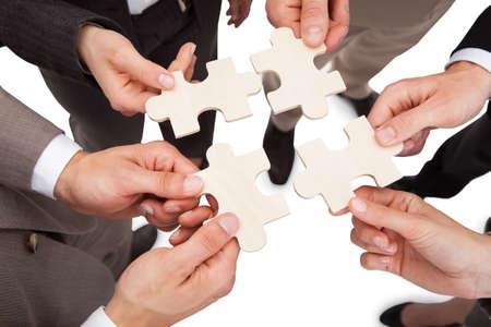 ハイアングル ビジネスの人々 の白でジグソー パズルのピースを修正します。