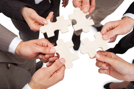흰색 위에 퍼즐 조각을 고정하는 사업 사람들의 높은 각도보기