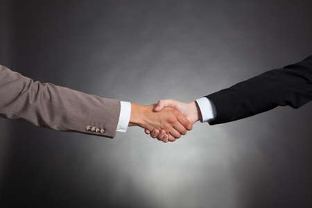 Cropped image of businessmen shaking hands against black  photo
