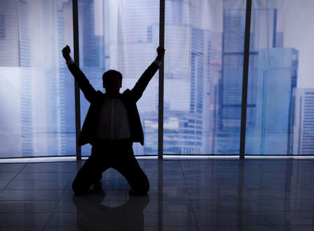 office window view: Full length rear view of businessman sitting arms outstretched by office window