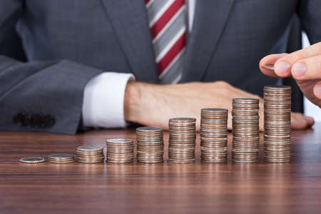 Midsection of businessman stacking coins in increasing order at desk photo