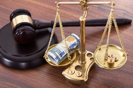 Judge gavel and scales with money on wooden desk photo