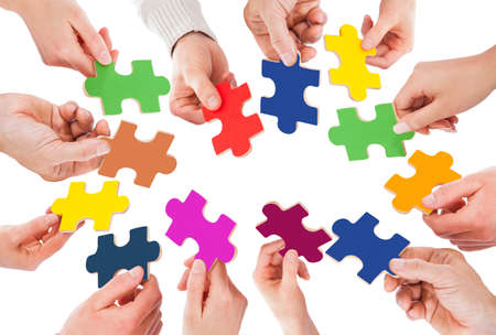 Cropped image of business people holding colorful jigsaw pieces over white  photo
