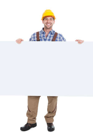 studio happy overall: Full length portrait of confident young manual worker holding billboard over white