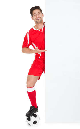 Full length portrait of young soccer player with football pointing at billboard over white  photo