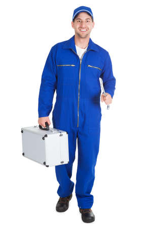 Full length portrait of happy worker with toolkit and wrench over white  photo