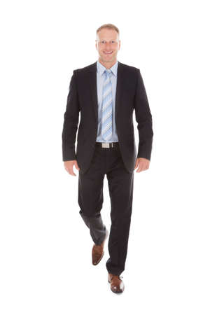 Full length portrait of confident mid adult businessman walking over white