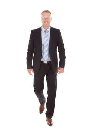 Full length portrait of confident mid adult businessman walking over white