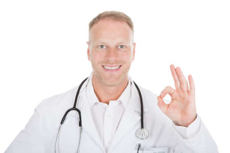 Portrait of smiling mid adult doctor with okay gesture over white  photo