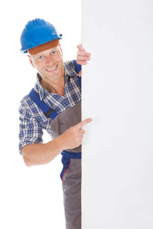 Full length portrait of confident young manual worker holding billboard over white