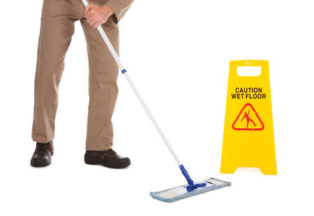 mopping: Low section of male servant mopping floor over white