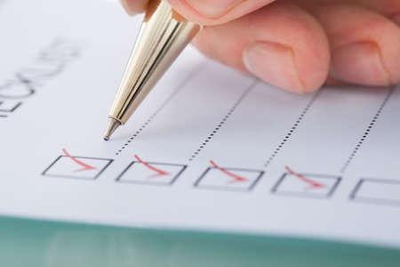 ビジネスマンのオフィスの机でチェックリストの準備の画像をトリミング