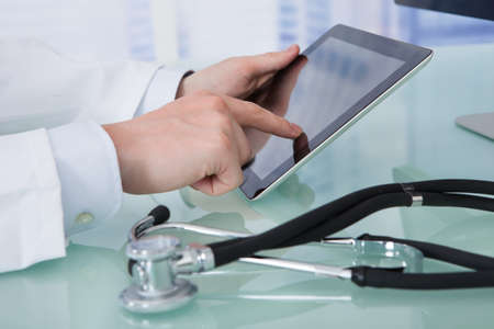 cropped image: Cropped image of young male doctor using digital tablet at desk in clinic