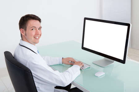 Portrait of confident young male doctor working on computer at desk in hospital Stock Photo