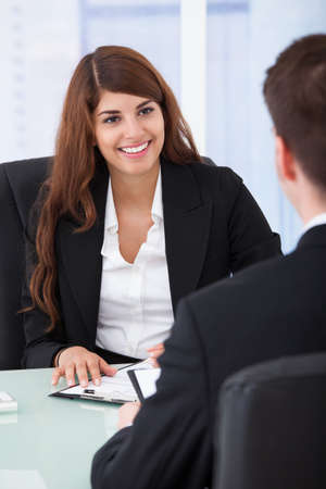 Happy young businesswoman interviewing male candidate at desk in office photo