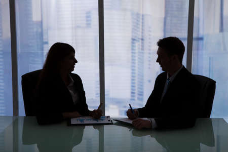 late 20s: Silhouette businessman and businesswoman discussing at desk in office