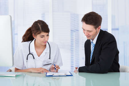 consulta médica: Joven doctora mostrando informe al empresario en la clínica