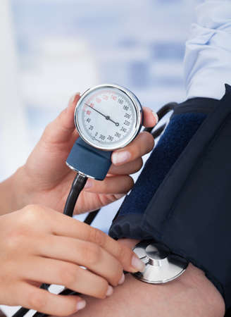 stethoscope exam: Cropped image of young female doctor checking blood pressure of businessman in clinic Stock Photo