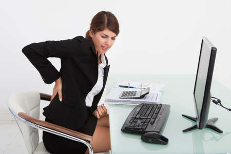 Tired young businesswoman suffering from backache while working at computer desk in office