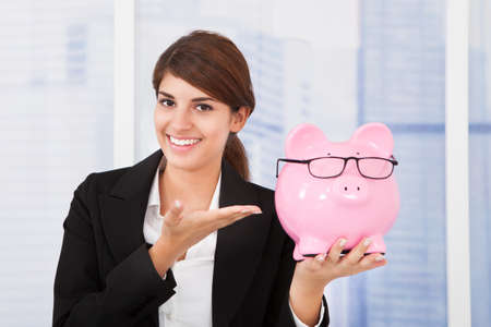 financial protection: Portrait of happy young businesswoman showing piggybank with eyeglasses in office
