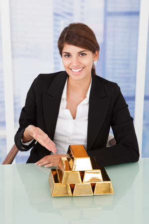 vertical bars: Portrait of confident businesswoman showing stacked gold blocks on desk in office