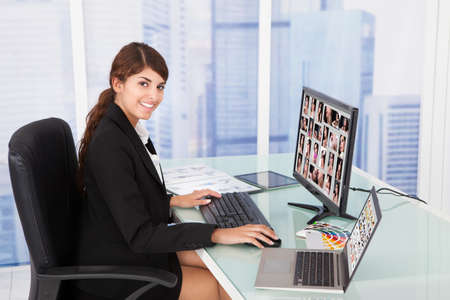 Young businesswoman looking at color swatches at computer desk in office photo