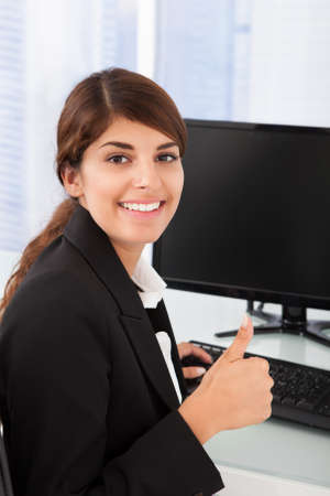 Portrait of happy businesswoman gesturing thumbs up at desk in office photo