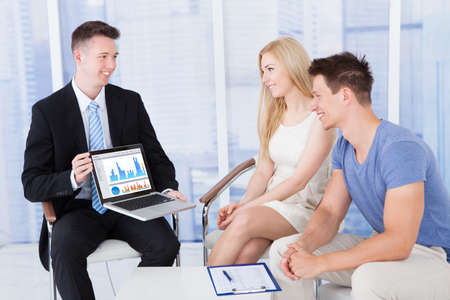 client meeting: Young financial advisor showing graph on laptop to couple in office