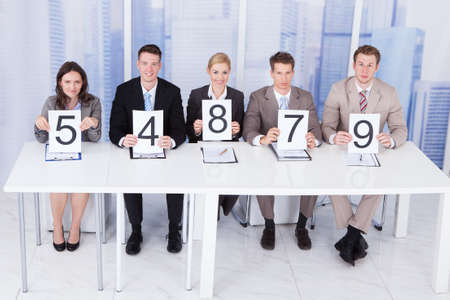 committee: Portrait of confident business people showing score cards