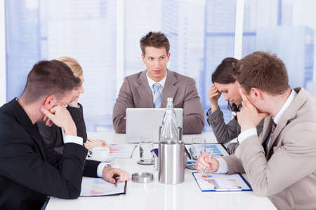 Young businessman looking at tired colleagues during conference meeting photo