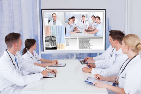 videos: Team of doctors having video conference meeting in hospital Stock Photo