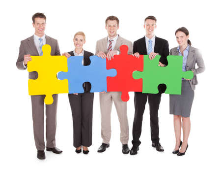 Full length portrait of confident young business people holding colorful jigsaw puzzle over white isolated