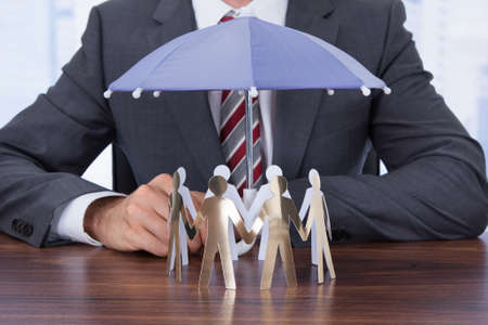 sheltering: Midsection of businessman sheltering paper people with umbrella at desk Stock Photo