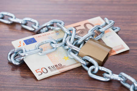 lock and chain: Fifty euro notes with chain and padlock on table
