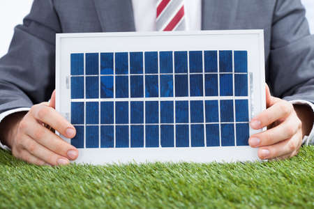 environmental conversation: Midsection of businessman holding solar panel on meadow