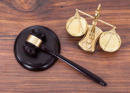 criminal justice: Judge gavel and scales with money on wooden desk