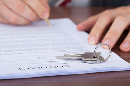 Cropped image of man signing contract with keys on it photo