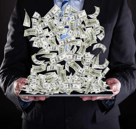Midsection of businessman holding digital tablet with American banknotes over black  photo