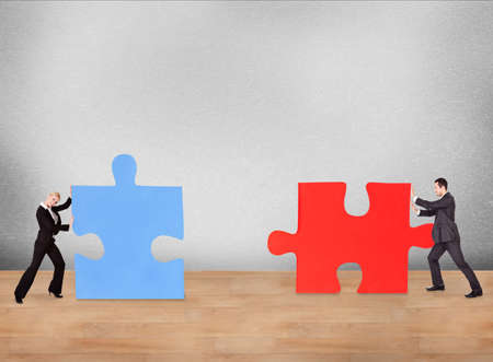 two piece: Business people joining puzzle pieces on desk