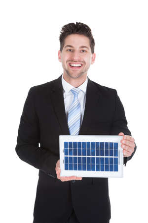 environmental conversation: Portrait of smiling mid adult businessman holding solar panel over white