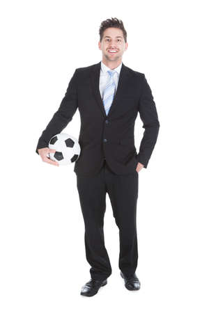 Full length portrait of confident young businessman holding soccer ball over white  photo