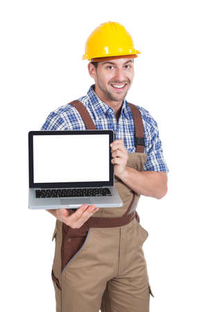 Portrait of young manual worker displaying laptop over white  photo