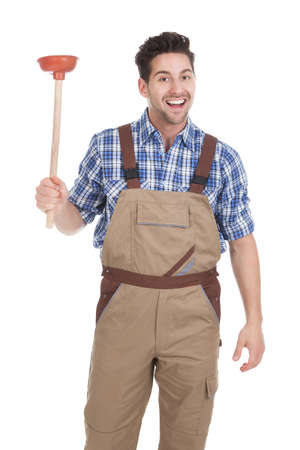 Full length portrait of excited young male plumber holding plunger over white  photo