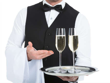 alcohol server: Midsection of waiter carrying champagne flutes on tray over white